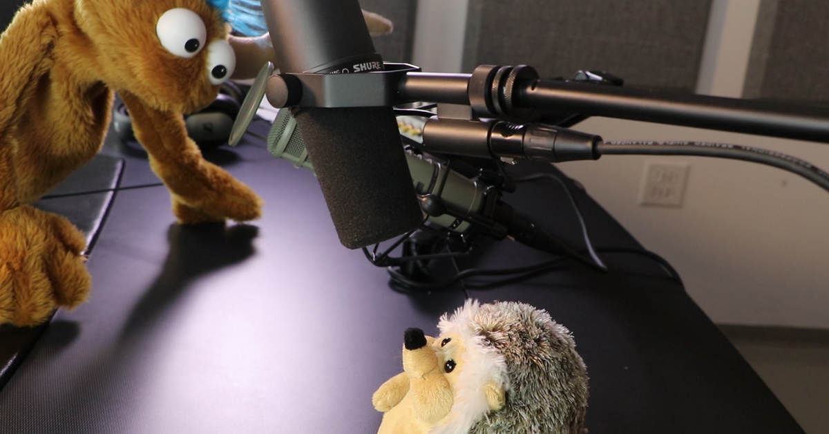Puppets recording a podcast