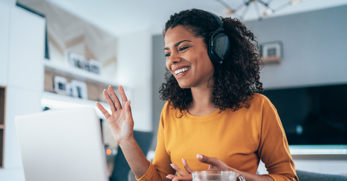 Virtual Event Tips: Woman smiling at computer with headphones on